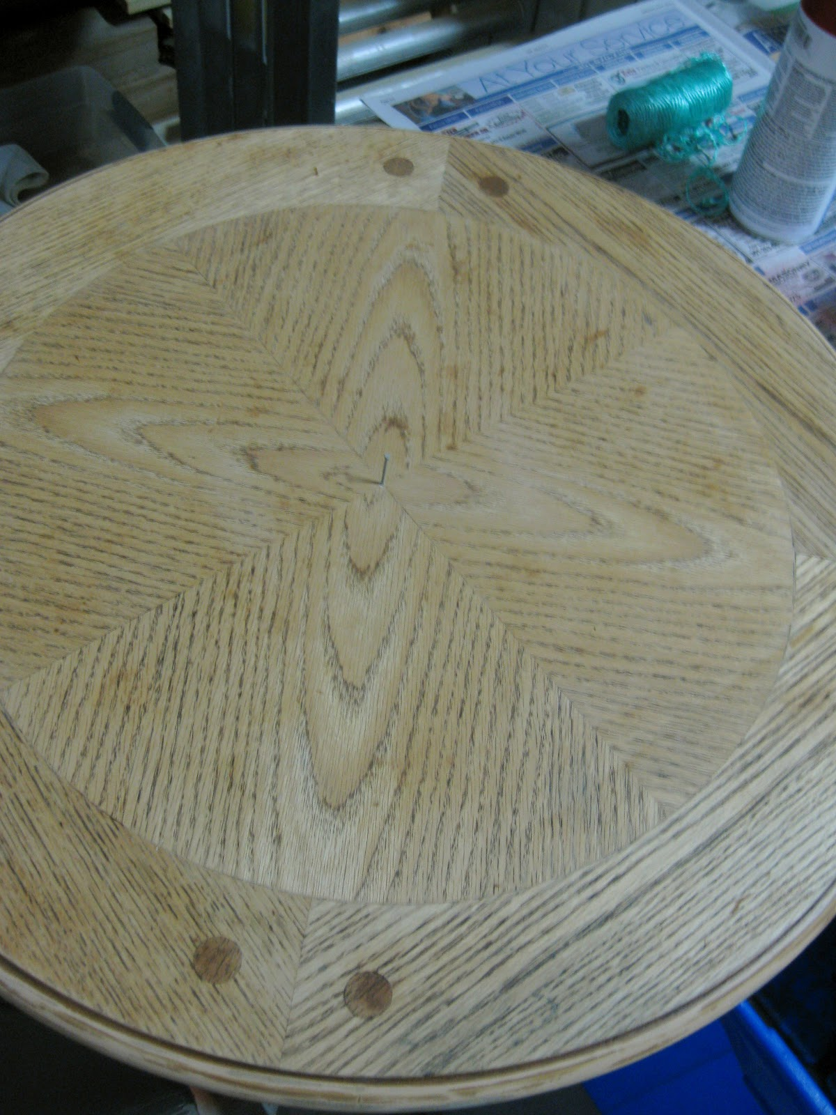oak round table top is sanded before being painted