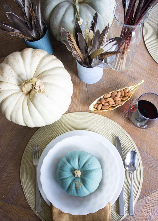 A modern Thanksgiving table with gold dipped feather arrangements and pumpkins painted in moody blues and greens || http://designimprovised.com