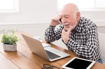 persona mayor conversando con un telefono movil y observando la pantalla de ordenador