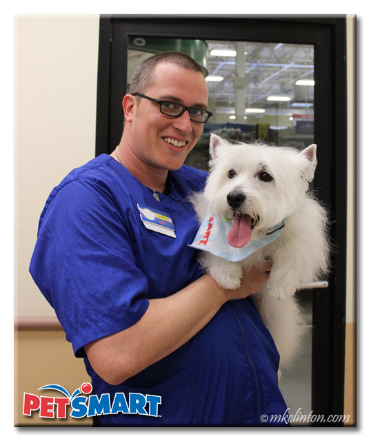Male PetSmart Groomer smiling with Westie in his arms