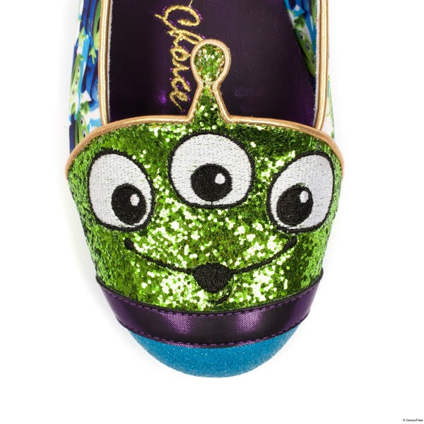 close up of green glitter alien face across toe of shoe on white background