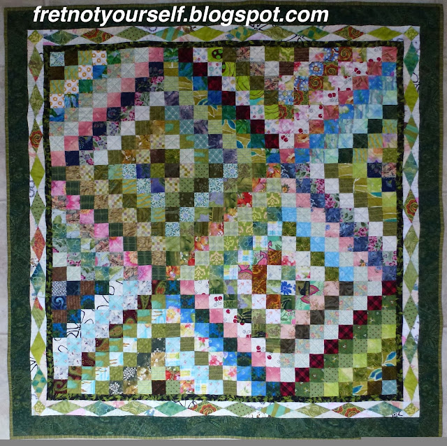 Scrappy Trip baby quilt with diamond border. Green and pink