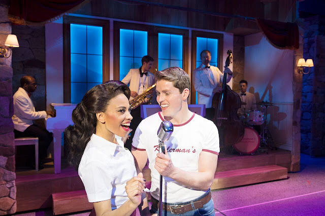 Danielle Pobega and Michael Kent share a microphone and sing as camp hosts in Dirty Dancing