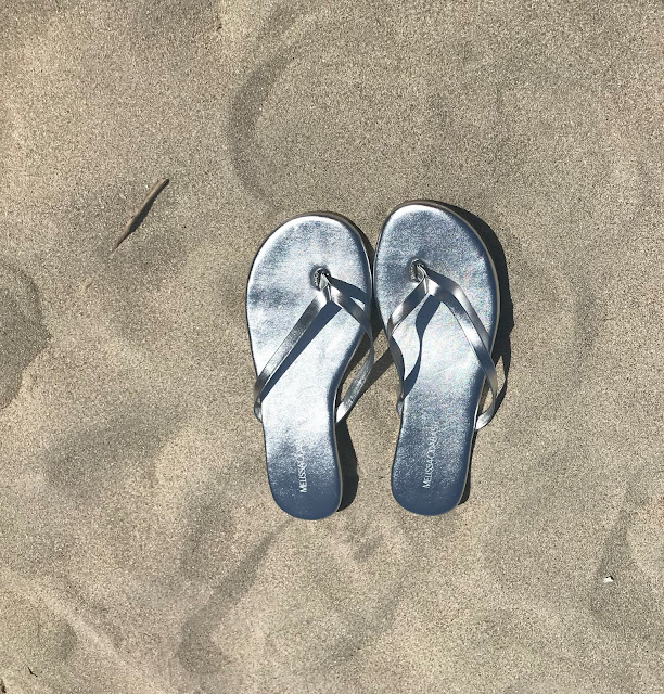 silver Melissa flip flops on the sand