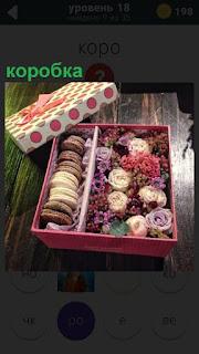 Лежит открытая коробка с печеньем и цветками внутри