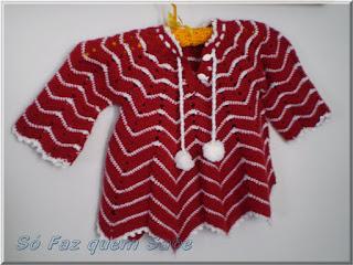 Foto mostrando um casaquinho feito em crochê pendurado num cabide depois de lavado e mostrando que ele se deforma quando pendurado.