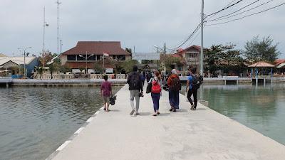 foto orang berjalan kaki di pinggir pantai