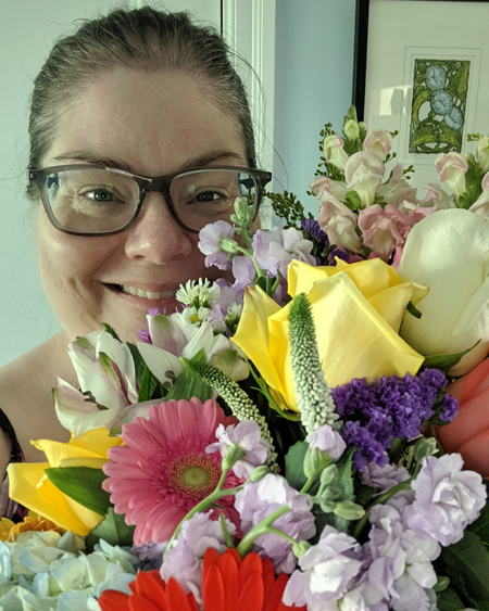 image of my grinning face peeking out from behind a large bouquet of flowers