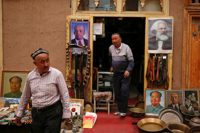 Image Attribute:  Portraits of China's late Chairman Mao Zedong, Soviet state founder Vladimir Lenin and German philosopher Karl Marx are displayed outside an antique shop in the old town in Kashgar, Xinjiang Uighur Autonomous Region, China, March 22, 2017.  REUTERS/Thomas Peter