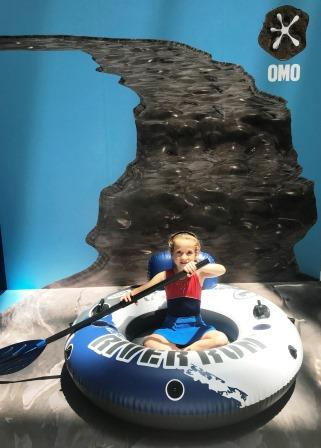 Girl in rubber dinghy on dirt river, with OMO logo in background