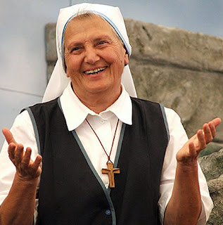 An image of Sister Elvira Petrozzi, smiling with her hands held out.