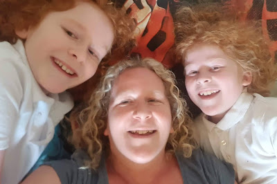 Top tips for better sleep selfie showing mum and two sons lying grinning on a child's bed