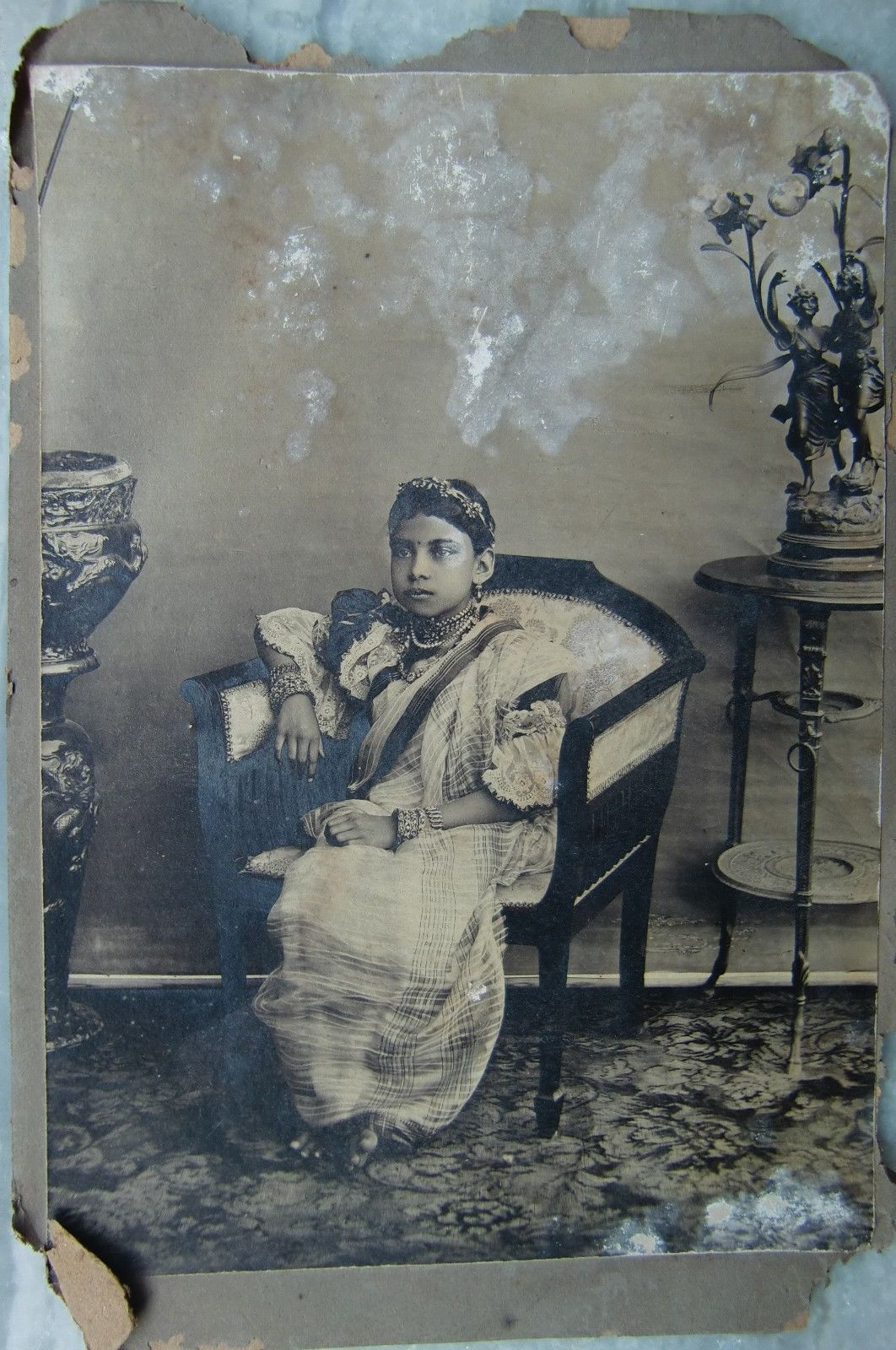 An Indian Girl in Sari Sited in a Chair