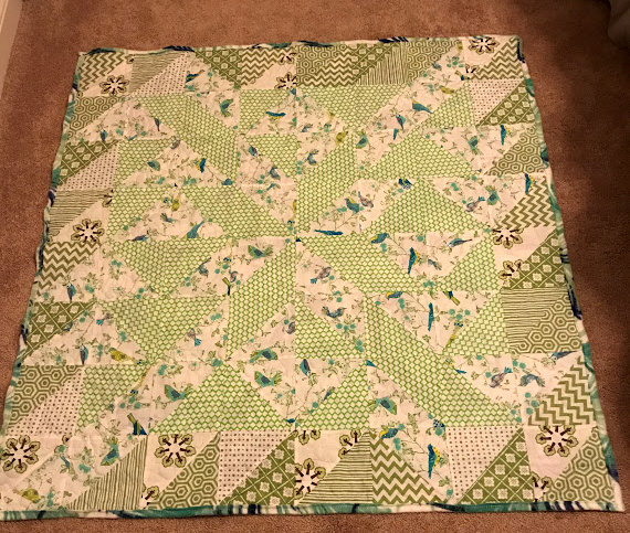 Pin wheel quilt in green and white.