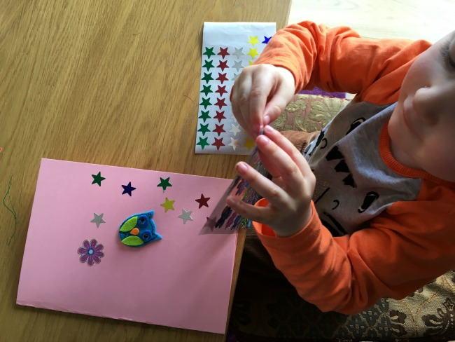 toddler peeling stickers from backing paper