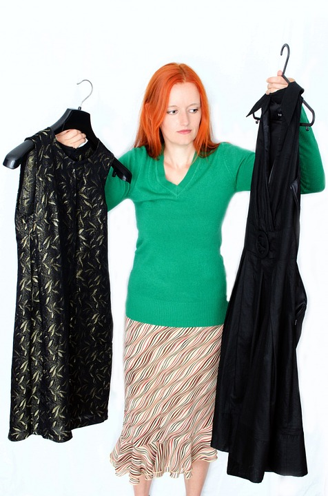 woman-inspecting-appropriate-dresses-for-work Pixabay image- to avoid wardrobe mistakes