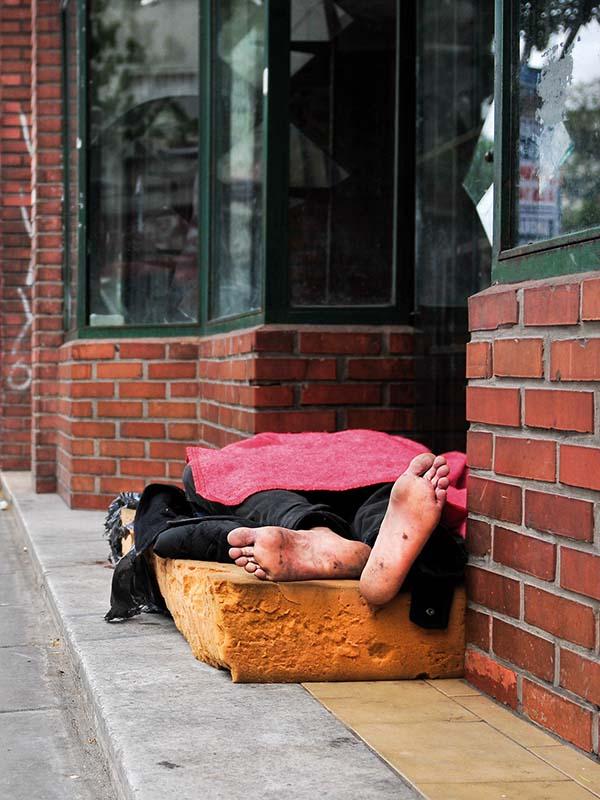 Un hombre descalzo duerme sobre un colchón roto en la vía pública