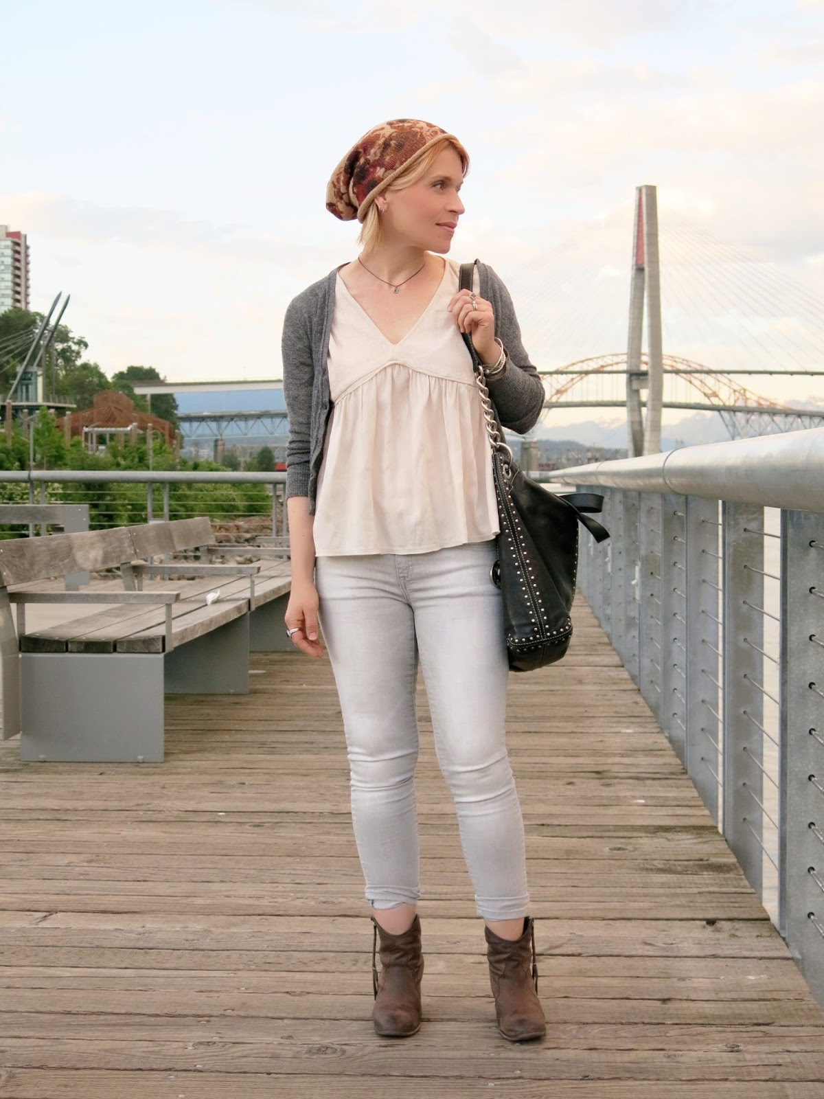 styling a drapey top with skinny jeans, western-style booties, shrunken cardigan, and floral beanie