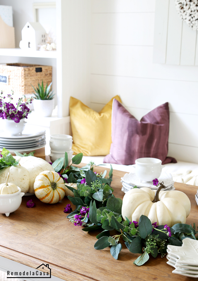 Table with greenery, white pumpkins and dishes and purple flowers