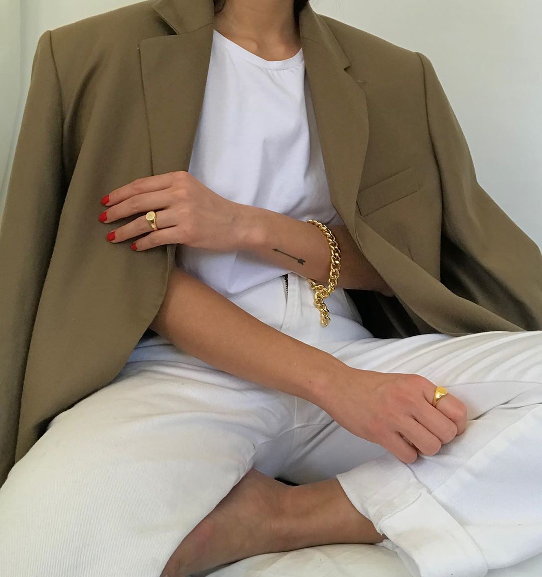 Neutral blazer, white t-shirt, signet rings, a chain bracelet, red nail polish, and off-white jeans