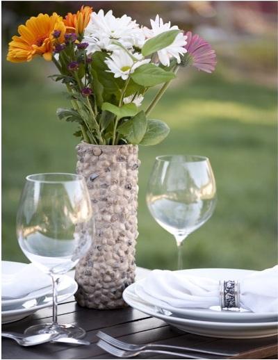 Buat sendiri vas bunga bergaya rustic dari bahan kaleng yang dihias batu-batu.