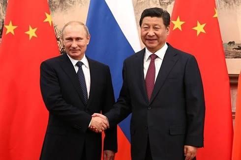 Tổng thống Nga Vladimir Putin (trái) hồ hởi bắt tay Chủ tịch Trung Quốc Tập Cận Bình