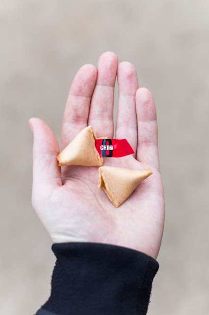 "Hand holding chinese fortune cookies and a note ""China 8"""