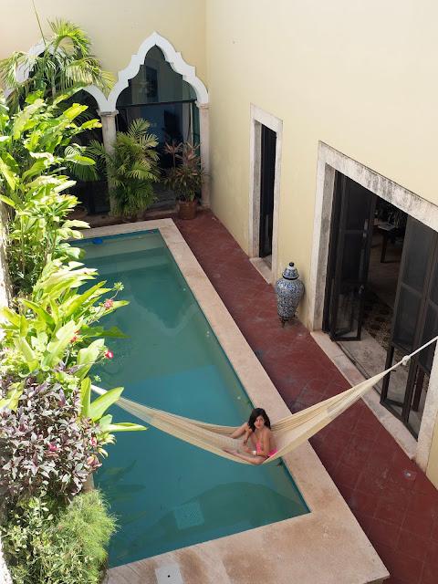 Niña sentada en una hamaca sobre una piscina en un patio de casa colonial con plantas