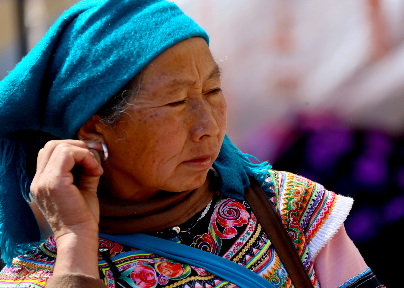 Mulher de uma tribo asiática, com brinco de prata e roupas tradicionais ilustra este post sobre o Shijing, o Livro das Canções.