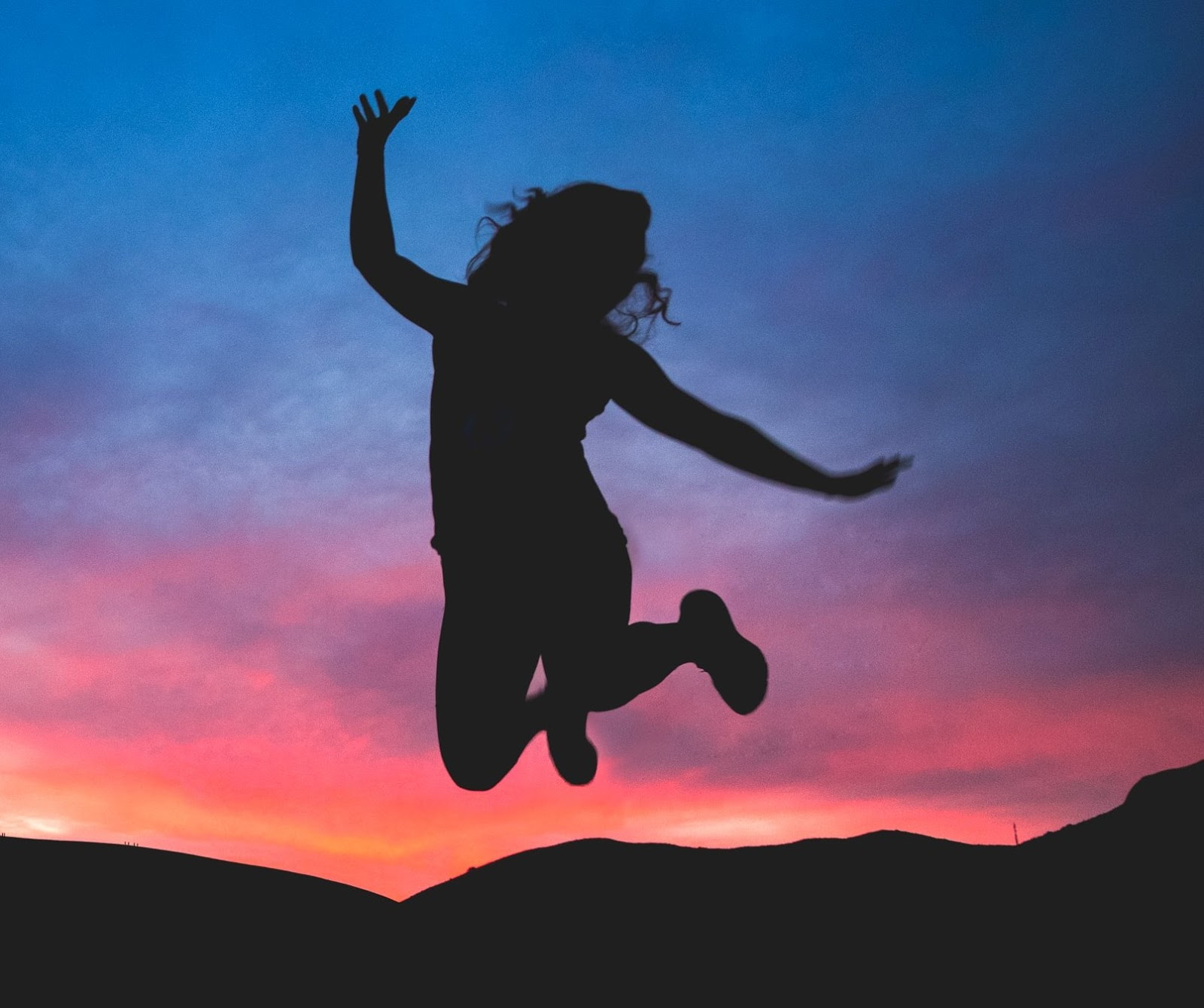 Photo of a silhouette of a person jumping in the air, arms outstretched, legs bent up behind them, against the backdrop of hills in silhouette and a orange, pink, purple and blue sunset