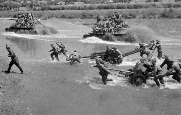 Soviet troops and heavy equipment fording a shallow river in Ukraine, 1944