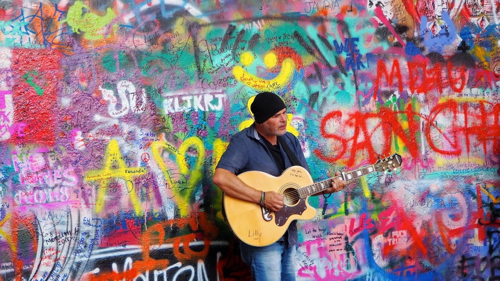 guitar player in front of John Lennon Wall in Prague