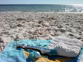 Crochet in progress on a long double-ended tricot hook is laid out on a beach towel next to a crocheted bag. The scene is a sandy beach looking across the water which has no surf, just gentle foam lapping at the shoreline.