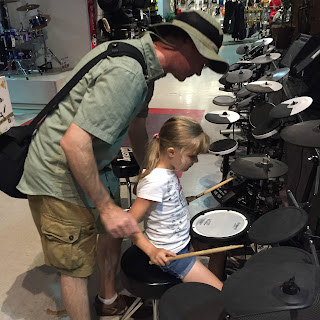 dad teaching daughter to play drums