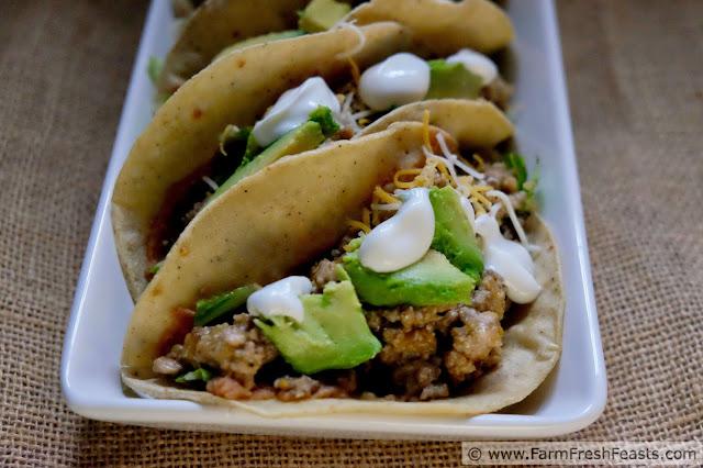 image of corn tortillas with refried beans, salsa verde pork, avocado and sour cream