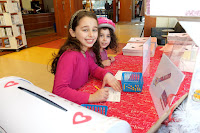 Two children filling out Library Lovers Month postcards
