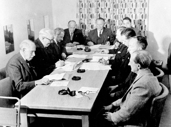 Photograph of the first meeting of North Mymms Parish Council held in the Memorial Hall 29 November 1957 Left to right: Cllrs W. Russell-Smith, B. W. Prettyman, G. T. Jackson, H. M. Alderman, C. W. Allison (chairman), M. G Woodend (clerk), R. O. Geekie, W. G Humphrey, R. Tingey, E. J Evans - Image from North Mymms Parish Council
