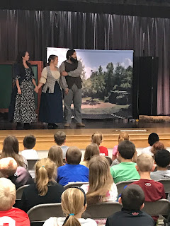 Two women and a man standing on stage for the Tecumseh Performance