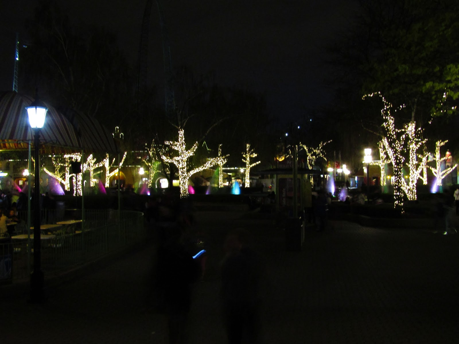 A view of International Street looking from the entrance to Medieval Faire. The trees are strung with white lights.