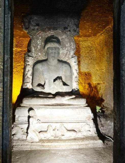 Buddha Idol in the Ajanta cave 11 - there is one devotee at the foot