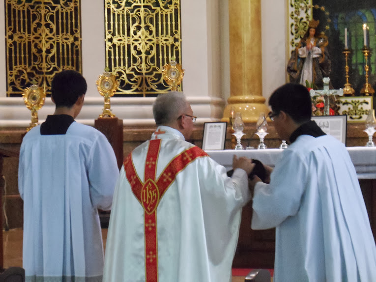 Priest receives his biretta from the server
