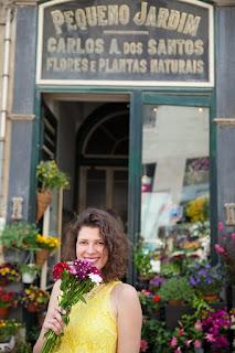 pessoa com blusa amarela na porta da floricultura pequeno jardim com flores na mão