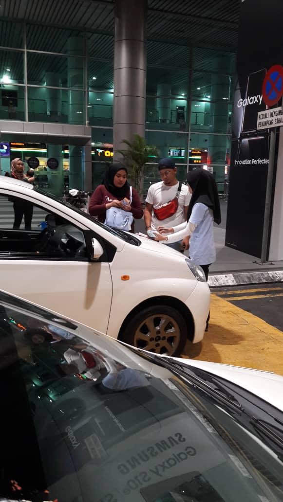 sewa kereta kota kinabalu sabah. seorang lelaki dan perempuan sedang membuat urusan penyerahan kereta sewa di lapangan terbang antarabangsa kota Kinabalu Sabah.