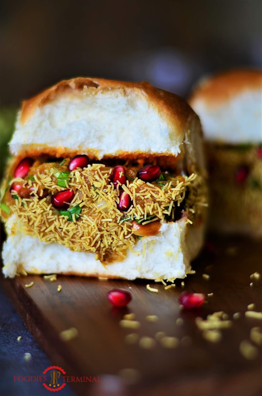 Home-made street style dabeli is ready, garnished with more pomegranate seeds and dusted with sev.