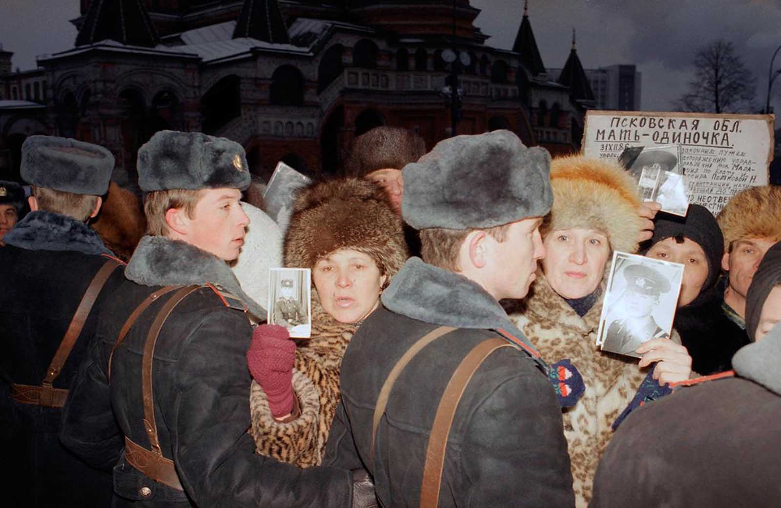 Soviet mothers who lost their sons in the Red Army are held back by State militia as they hold photographs of their loved ones in Red Square, on Monday, December 24, 1990. A group of about 200 Soviet parents who have all lost sons through ethnic violence and accidents within the Soviet armed services demonstrated outside the Kremlin. 6,000 Soviet service men were killed during 1990.