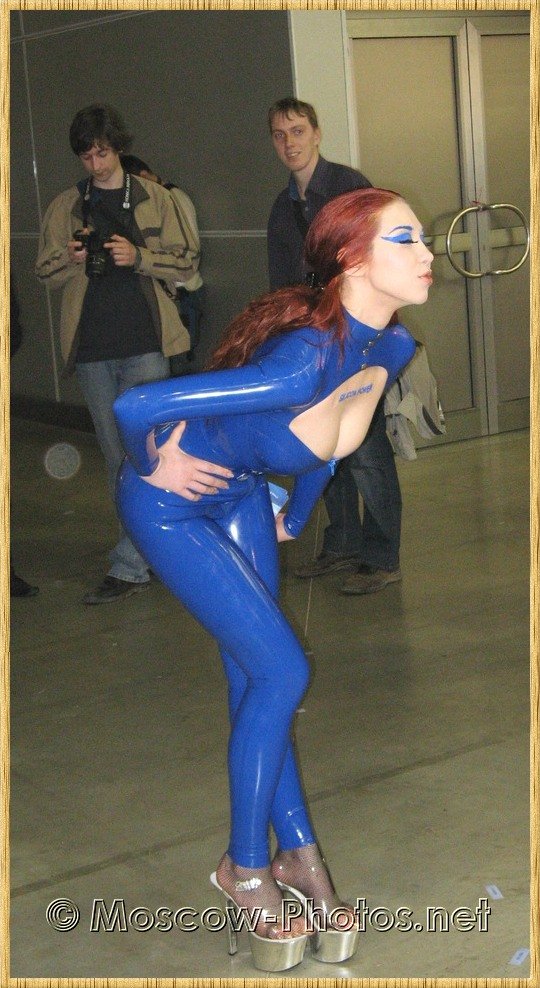 Redhead model girl in rubber suite posing