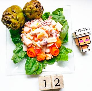 dos alcachofas enteras, tiras de zanahoria dando la impresión de ser rosas, ensalada de pulpo en el centro de la imagen rodeado de espinacas