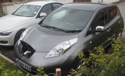 A Nissan Leaf electric car charging outside a solar eco-house.