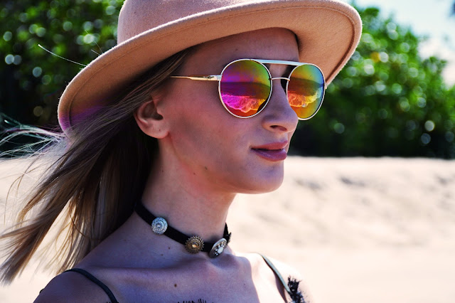 sea reflected in round rainbow sunglasses blogger look with boho choker
