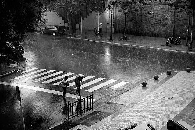 Una pareja corre bajo una intensa lluvia, en Blanco y Negro